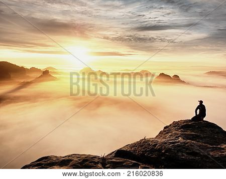 Adult Tourist In Black Trousers, Jacket And Dark Cap Sit On Cliff's Edge And Looking To Misty Hilly
