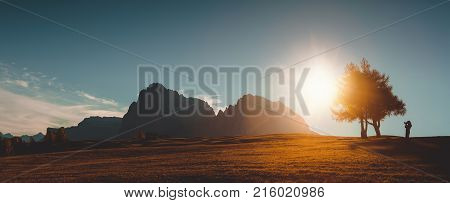 Autumn sunrise scenery with small alpine building and Odle - Geisler mountain group on background. Alpe di Siusi (Seiser Alm) Dolomite Alps Italy.