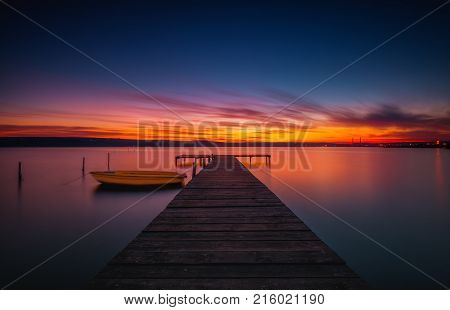 Wooden Dock And Fishing Boat At The Lake, Sunset Shot