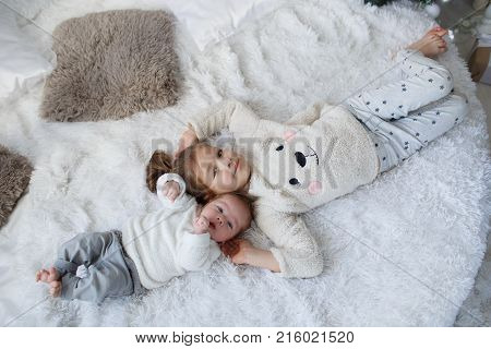 Little girl embracing a  newborn baby brother. Little girl and baby boy brother and sister playing in parents bed.Cute girl and a newborn boy resting together in a white bedroom. Family with children at home. Love, trust and tenderness