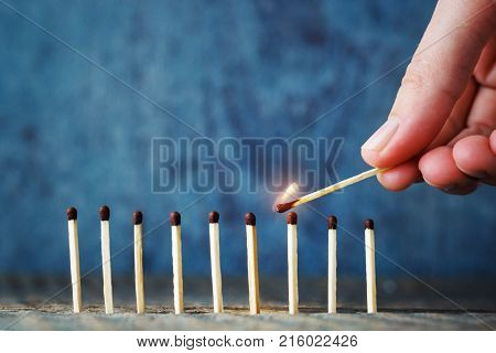 A lit match in hand tries to set another match on fire. The concept of unity and mutual assistance. Burning match on a wooden blue background