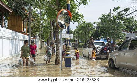 November 25, 2017 : People Walking Through Flooded Streets To Get Donations  Phetchaburi, Thailand