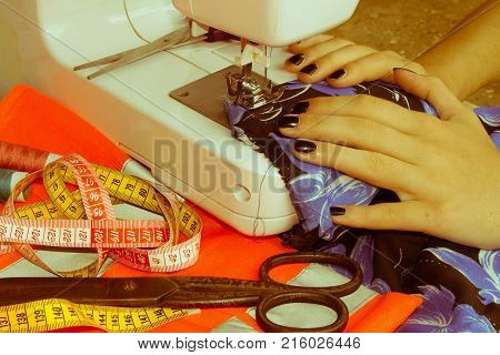 processes of sewing on the sewing machine sew women's hands sewing machine. Female tailor threading leather material on sewing machine. designer making a garment in her workplace