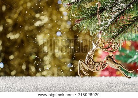 Christmas Golden reindeer. Falling snow winter scene. Place for text. Reindeer of Santa Claus.