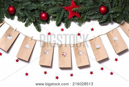 Handmade Tinkered Advent Calendar With Paper Bags And Stickers Hanging From Fir Branches And Red Sta