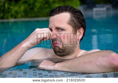 young man with disgust on his face pinches nose, something stinks, very bad smell in swimming pool because of chloride. Negative emotion facial expression