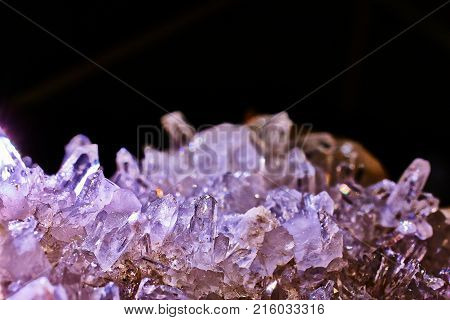 Mountain crystal stone, purple look, on a black background, natural phenomenon, closeup photograph. Also known as rock crystal.
