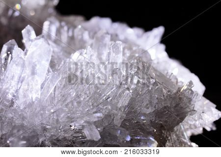 Mountain crystal stone on a black background, natural phenomenon, closeup photograph. Also known as rock crystal.