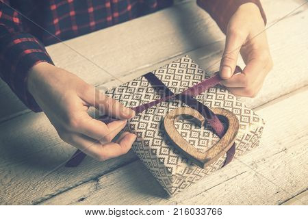 woman wrapping a gift for beloved. tying a ribbon bow with wooden heart decor