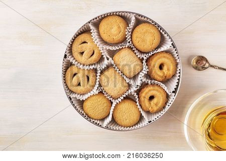 An overhead photo of a tin can of Danish butter cookies with a cup of tea on a light background, with a vintage spoon with caramelized sugar, and a place for text