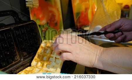 Viennese waffles waffle iron pile of orange. Man prepares Viennese waffles in the kitchen. ooking Viennese waffles.