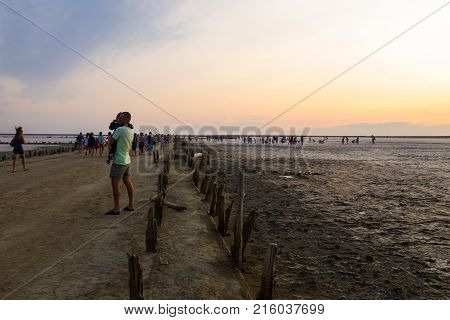Genichesk, Ukraine - August 23 2017: People gathering salt of pink salty Siwash Lake colored by microalgae famous for antioxidant properties enriching water by beta-carotene at sunset