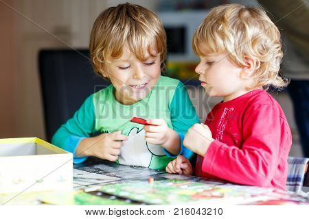 Two little blond kid boys playing together board game at home. Funny siblings having fun. Twins and best friends, toddlers learning interact, win and lose.