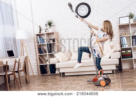 The woman vacuums the apartment. A woman is having fun while cleaning an apartment. A young woman fools around with a vacuum cleaner.