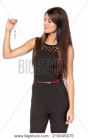 Smiling elegant business woman in black holding pendant sewing in her fingers, over white background
