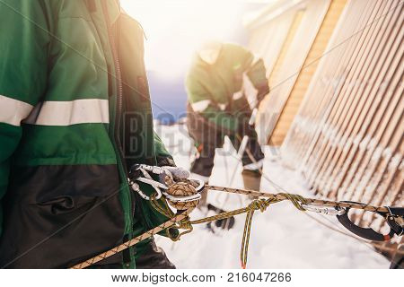 Close-up of safety belt and carbine concept of cleaning roofs from snow in winter