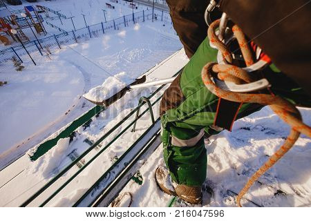Clean snow. A man with a shovel cleans roof of building from snow ice with shovel. Safety harness mounting shell.