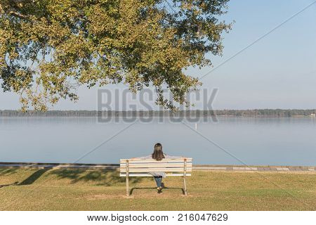 Back View Young Asian Woman Sitting On A Bench Near The Calm Water Of Houston Lake