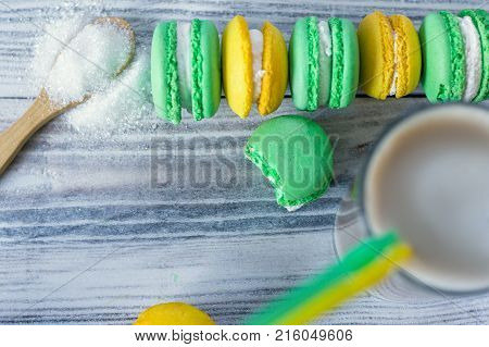 colorful macaroons are laid in a row and latte in a glass