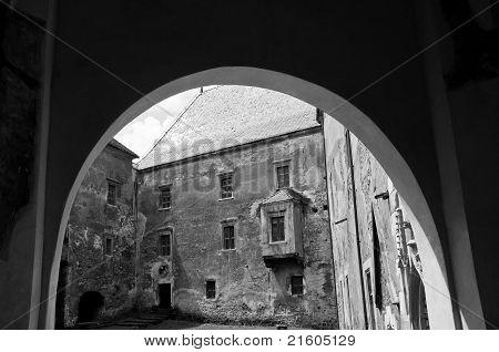 View through an arch towards a stone castle courtyard