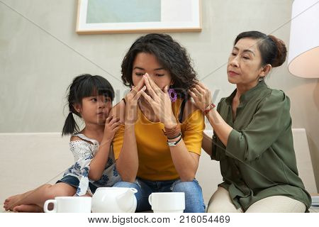 Crying Vietnamese woman being reassured by her daughter and senior mother