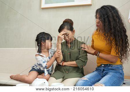 Daughter and grangdaughter reassuring senior Vietnamese woman