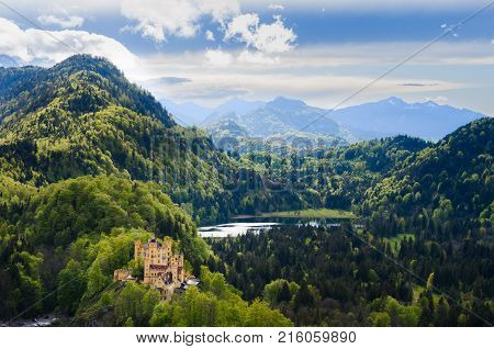 Panorama of the Alpsee lake and its forest under a partially cloudy sky near Neuschwanstein in Bavaria Germany.