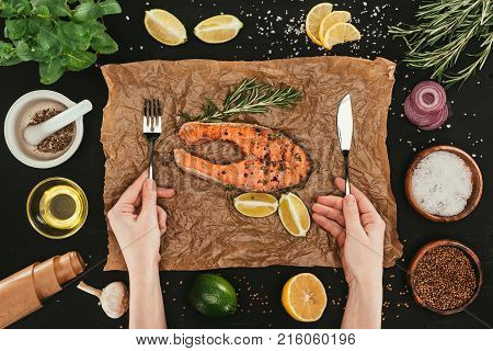 cropped shot of person with fork and knife eating salmon steaks