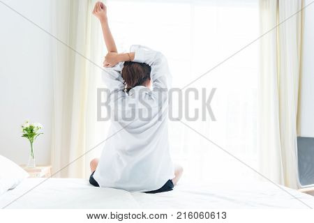 Back View Of Woman Stretching In Morning After Waking Up On Bed Near Window. Holiday And Relax Conce