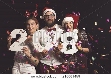 Three young friends having fun at New Year's Eve Party holding cardboard numbers 2018