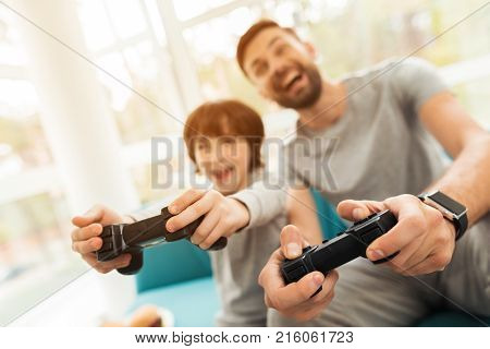 Father and son play together in computer games. In their hands they have joysticks for game consoles. They got carried away by the game. They have a lot of excitement.