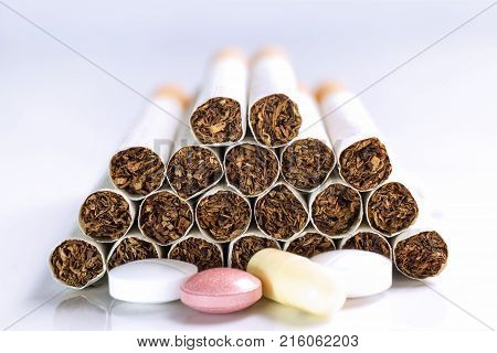 Cigarette and Medicine on a white table. Smoking causes cancer and emphysema. Health Care concept.