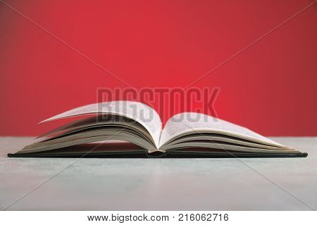 Composition with vintage old hardback books, diary, fanned pages on wooden deck table and red background. Books stacking. Back to school. Copy Space. Education background