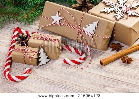 Christmas time concept Christmas gifts and traditional New Year sweets candy cane on wooden bachground. Top view copy space.