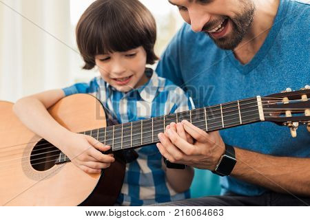 The father teaches his son to play the guitar. He helps him pick up guitar chords. They are in a good mood.