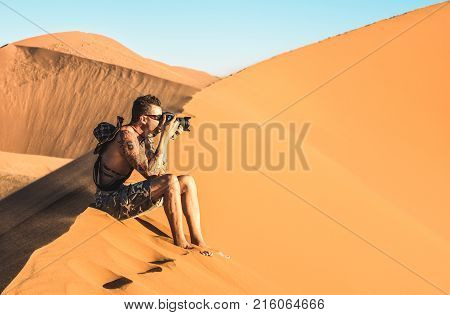 Lonely man photographer sitting on sand at Dune 45 in Sossusvlei - Concept of wanderlust in namibian famous desert - Adventure trip travel to african wonders in Namibia - Soft teal and orange filter