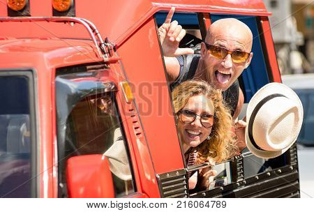 Happy couple of tourist travelers around Patong with tuk-tuk taxi car - Wander friends having fun on road trip in Phuket island Thailand - Travel concept with adult people on world tour - Warm filter