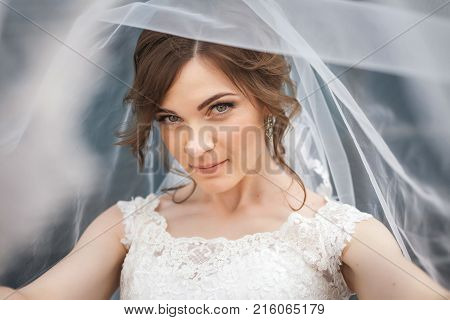 Portrait of attractive, young bride with white veil over her face. Concept of young gorgeous bride looking to the camera.