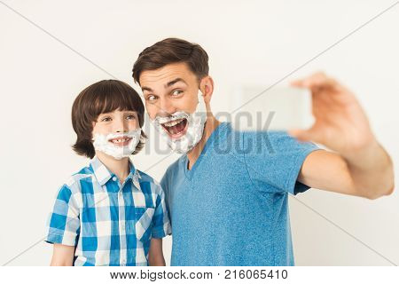 The father shows his son how to shave in the bathroom. The boy smeared with foam for shaving. They do selfie on a smartphone. Both of them were very lucky.
