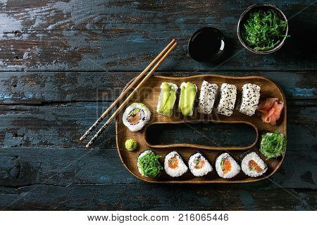Homemade sushi rolls set with salmon, sesame seeds and avocado serving in wood plate with pink pickled ginger, soy sauce, wasabi, seaweed salad, chopsticks over dark wooden background. Top view, space