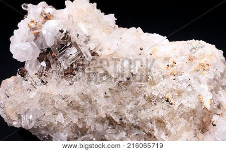 White transparent quartz natural crystals with glittering peaks on a black background. Natural phenomenon. Mountain crystal.