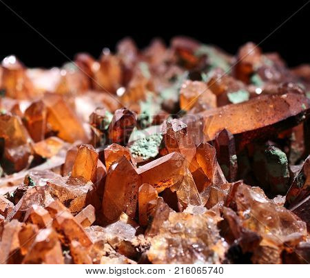 Brown translucent natural crystals with glittering peaks on a black background. Natural phenomenon.
