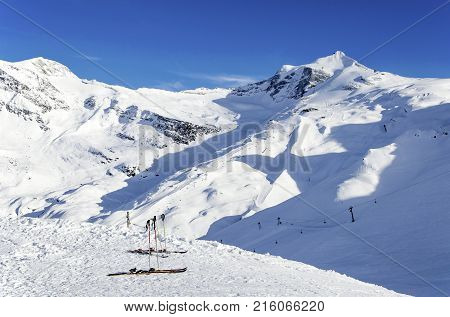 Two pairs of skis ski poles ski lifts and pistes and Hintertux Glacier in Zillertal Alps in Austria at sunset light