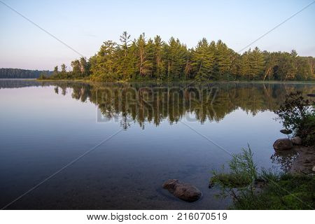 Northern Michigan Wilderness Lake. Wilderness lake with forest reflections in the water and copy space in the foreground in Mio, Michigan.