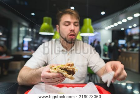 A man is sitting in a restaurant and eating fast food. The man eats an appetizing burger. Fast Food Concept. Focus on the burger