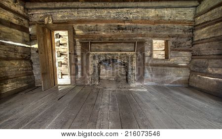 Pioneer Log Cabin Interior. Wooden interior of historic pioneer cabin living room with hardwood floor and fireplace.