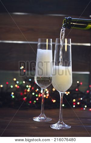 A festive still life with two wine glasses on a dark colored wooden background. Champagne is being poured into a glass from a bottle. Dark colorful bokeh