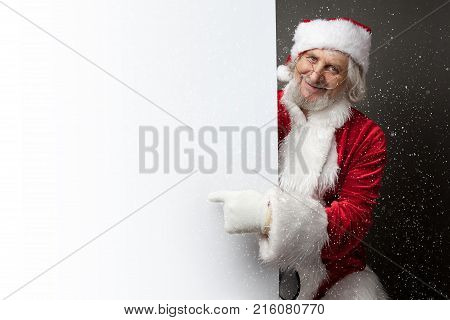 happy Santa Claus showing something on a white wall