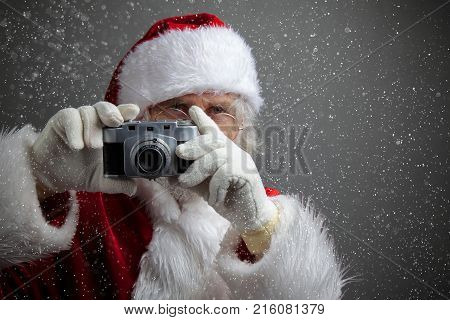 Santa Claus taking picture with old camera. dark background with snow
