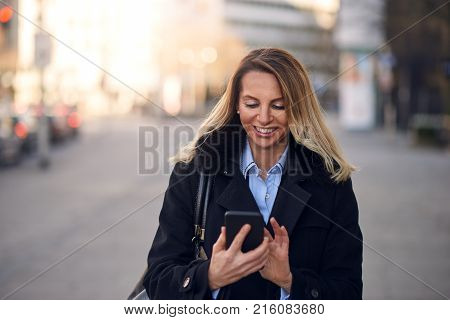 Fashionable Woman Busy With Phone At City Street